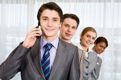 Calling leader. Photo of happy leader calling his partner with smiling employees looking out of his back Stock Photography