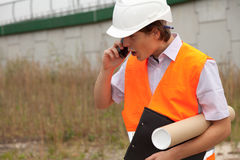 Calling male architect with blueprint Royalty Free Stock Photo