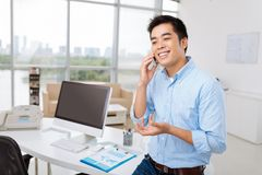 Calling manager. Young Asian manager standing at his workplace and calling on the phone Stock Photo