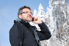 Calling mountaineer. Calling phoning mountaineer tourist in winter mountains stock photos