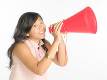 Calling Out. Young woman calling out cheerful with a red plastic cone Royalty Free Stock Photography