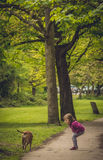 Calling out a dog. Cute girl looking at a dog at the park on summer day Stock Photo