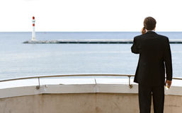 Calling Overseas. A business man standing on a balcony and talking on the mobile phone with a glass of champagne in his hand while looking at the sea with a Royalty Free Stock Photos