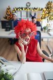 Calling on the phone. Business lady in funny red wig and sunglasses calling on the phone Royalty Free Stock Photo
