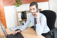 Calling phone businessman sitting in the office and using his laptop while working on new project. Portrait of calling phone businessman sitting in the office Royalty Free Stock Photo