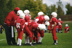 Calling the play. A young quarterback gives his team the gameplan before they line up Royalty Free Stock Photo