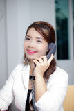 Calling and smiling. Asian woman worker smile while using telephone Stock Images