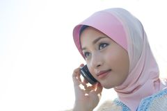 Calling some one. A young girl wearing scaft is making phone calls Royalty Free Stock Photo
