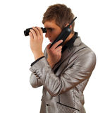 Calling spy man looking through binoculars Royalty Free Stock Image