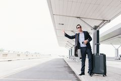 Calling a taxi. Attractive businessman calling a taxi at the airport Stock Photos