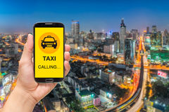 Calling Taxi message on a mobile phone screen. Hand holding smart phone on city background Stock Photos