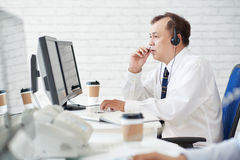 Calling to client. Professional financial analyzing in headset talking to client Stock Photo
