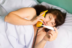 Calling to doctor.  Woman lying on bed Stock Photography
