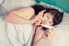 Calling to doctor.  Woman lying on bed Stock Photo