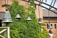 Calling to prayer. Church bells hanging outdoor. Metal bells on metallic chains hung on arc in church yard. Bells ringing on wind. Calling to christian mass or stock photo