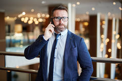 Calling for urgent question. Businessman calling to his colleague in business center Royalty Free Stock Photo