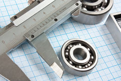Calliper and a bearing. A calliper and a bearing on graph paper stock image