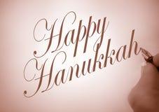 Callligraphy Happy Hanukkah. Person writing Happy Hanukkah in calligraphy with  sepia tone Royalty Free Stock Photos