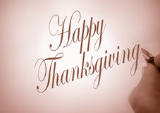 Callligraphy happy thanksgiving. Person handwriting happy thanksgiving in calligraphy in sepia tone royalty free stock photo