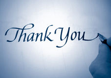 Callligraphy thank you. Person writing thank you in calligraphy in blue tone royalty free stock photos
