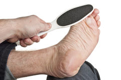 Callus removal. From toe ball on foot resting on knee Royalty Free Stock Images