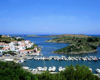 Calm. Sailboats in an inlet on the Spanish island of Minorca with villa's in the background royalty free stock photography