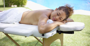 Calm adult female laying down on massage table Royalty Free Stock Photos