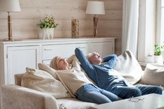 Calm aged couple sleeping on couch relaxing at home. Peaceful elderly couple sleep on cozy couch spending weekend in countryside, calm senior husband and wife royalty free stock photography