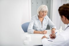 Calm aged woman looking at the notes of her general practitioner stock photography