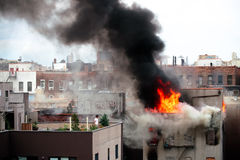 Calm as the Flames. Man stands around casually as there is a raging fire on his neighboring building in Spanish Harlem Royalty Free Stock Photography
