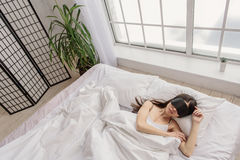 Calm asian female sleeping in bed. Sweet dream. Top view of serene young woman with covered eyes lying on white cushions in room. Sleep concept Stock Photos