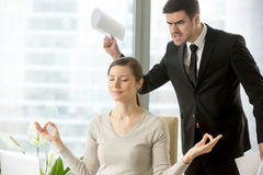 Calm attractive businesswoman meditating in office, ignoring ang. Calm attractive businesswoman practicing yoga at work, meditating in office with eyes closed Royalty Free Stock Images