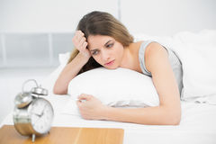 Calm attractive woman lying thoughtful on her bed. In the bedroom Stock Images