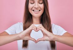 Calm attractive woman smiling slightly and shows fingers heart