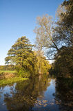 Calm Autumn day on the water. Small lake with trees in autumn colours and clear blue sky Stock Photography