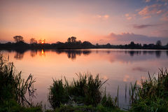 Calm autumn sunrise over wild lake Stock Photos