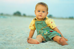 Calm baby boy sitting on evening beach Stock Photos