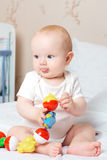 Calm baby boy with tongue holds the toy. Royalty Free Stock Images