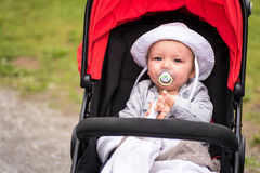 Calm baby with sun hat and pacifier sitting in his stroller Royalty Free Stock Photo