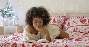 Calm beautiful African woman reading in bed stock footage
