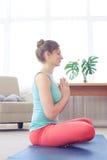Calm beautiful girl meditating while sitting on yoga mat on yoga Royalty Free Stock Images