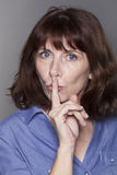 Calm beautiful mature woman wanting to keep things confidential Stock Photo