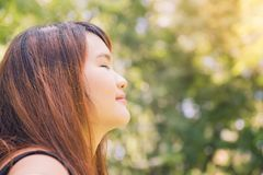 Calm beautiful smiling young woman with ponytail enjoying fresh air outdoor, relaxing with eyes closed. Feeling alive, breathing, dreaming. Copy space, green Royalty Free Stock Images