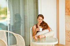Calm beautiful woman relaxing on terrace. With cup of coffee royalty free stock photo
