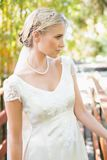 Calm blonde bride in pearl necklace standing on a bridge Stock Photos