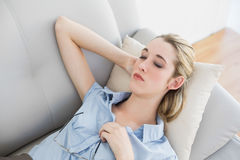 Calm blonde businesswoman lying sleeping on her couch Royalty Free Stock Photography