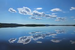 Perfect reflection from a Lapland lake. Calm blue Lake Äkäsjärvi reflecting white clouds in Finnish Lapland royalty free stock image