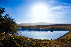 Calm blue lake, with blue skies. And white clouds above Royalty Free Stock Photography