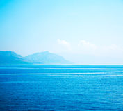 Calm Blue Sea with Mountains in Haze. Seascape. Royalty Free Stock Photo