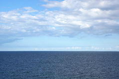 Calm blue sea. In summer with white clouds in the background Stock Image